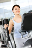 Girl on the xtrainer at the gym Royalty Free Stock Photos