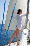 The girl on the yacht. The girl stand on the yacht undertaken a mast against a sail and the sea Royalty Free Stock Photos