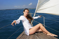 The girl on the yacht. The girl sits on the yacht undertaken a mast against a sail and the sea Stock Images