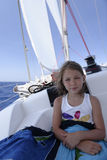 Girl on yacht. Portrait of a pretty young girl sitting on the deck of a yacht under sail Stock Photography