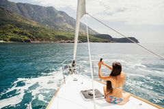 Girl yachting with smartphone photograph cruise Stock Photos