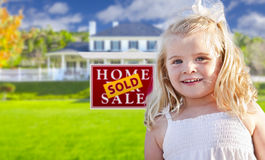 Girl in Yard with Sold Real Estate Sign and House Royalty Free Stock Image
