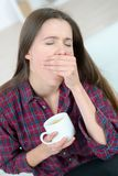 Girl yawing and holding cup Royalty Free Stock Photos