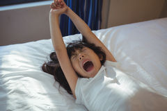 Girl yawning on bed in the bed room Stock Images