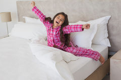 Girl yawning while stretching her arms in bed Royalty Free Stock Image