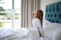 Girl yawning while waking up n bed Stock Photography