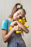 Girl. 11 year old girl gently huggs her yellow toy bear Royalty Free Stock Photography
