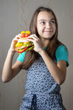 Girl. 11 year old girl with a hamburger in hand looking up with the question of whether to eat junk food Stock Image