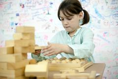 Schoolgirl playing with wooden puzzles. Girl of 7 years collecting   wooden puzzle in   playroom royalty free stock image