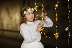 Girl of 8-9 years with delight admires gold Christmas-tree decorations. Stock Images