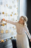 Girl of 8-9 years with delight admires gold Christmas-tree decorations. Stock Photo