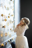Girl of 8-9 years with delight admires gold Christmas-tree decorations. Royalty Free Stock Photography