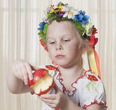 The girl of 4 years  eats red apple Stock Images