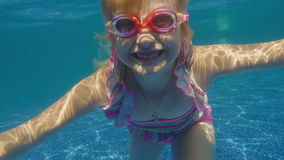 Girl 6 years of fun in the pool, dives. Underwater video. Girl 6 years old learns to dive in the pool. Slow motion video stock video footage