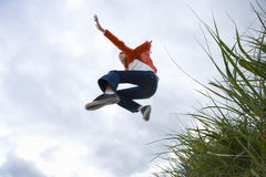 Girl (7-9 years) jumping from grass outdoors, low angle view Royalty Free Stock Image