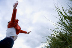 Girl (7-9 years) jumping from grass outdoors, low angle view Royalty Free Stock Photography
