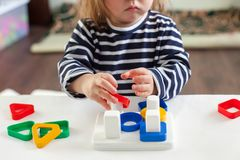 A girl of 1,5 years with long hair in a striped dress sits at the table and plays with a developing toy. Child 1,5 years old sitting at the table and playing Stock Photography