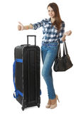 Girl 16 years old in jeans and a plaid shirt, hitchhiking. Teen girl 16 years old, with a big, black travel bag on wheels. Girl hitchhiking. Girl 16 years old in Royalty Free Stock Image