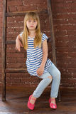 Girl 6 years old in jeans sits on a ladder near wall Stock Photos