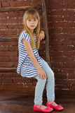 Girl 6 years old in jeans and vest sits on a ladder near wall Stock Images