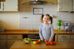 Girl 8-9 years old in the kitchen slicing vegetables for a salad. Stock Photo