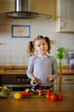 Girl 8-9 years old in the kitchen slicing vegetables for a salad. Stock Photos