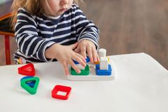 Child 1,5 years old sitting at the table and playing with a developing toy, Montessori technique, the child`s hands are busy play. Girl 1.5 years old with long royalty free stock photography
