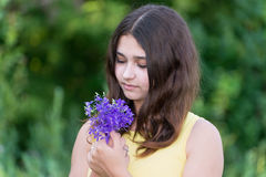 Girl 14 years old looking at bouquet of wildflowers Royalty Free Stock Photos
