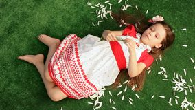 Girl 6 Years Old Lying on the Grass and Separates stock video footage