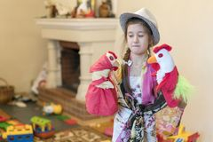 Girl 8 years old playing with dolls on the background of the fireplace royalty free stock photography
