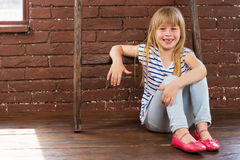 Girl 6 years old sits on the floor next to a brick wall and filled with laughter Royalty Free Stock Image