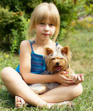Girl 6 years old sitting on the grass with Yorkshire Terrier Stock Photo