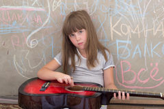 Girl 6-7 years old, sitting with a guitar Stock Photos