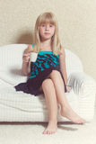 Girl 5 years old sitting on a sofa with cup. Girl 5 years old sitting on a sofa in a dress with a cup in hands Stock Photos