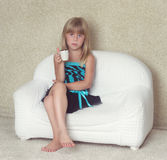 Girl 5 years old sitting on a sofa with cup Royalty Free Stock Photos