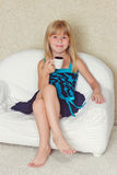 Girl 5 years old sitting on a sofa with cup. Girl 5 years old sitting on a sofa in a dress with a cup in hands Stock Images