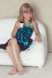 Girl 5 years old sitting on a sofa with cup. Girl 5 years old sitting on a sofa in a dress with a cup in hands Royalty Free Stock Image