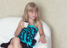 Girl 5 years old sitting on a sofa with cup. Girl 5 years old sitting on a sofa in a dress with a cup in hands Royalty Free Stock Photos