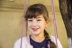 Girl 10 years old with a smile in the summer on a village swing stock photo