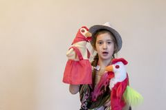 Girl 8 years playing in the puppet theater. Against a light background. copy space.  Royalty Free Stock Image