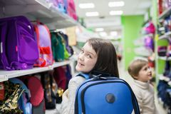 Girl of 8 years in shop choosing briefcase for school. First grader choosing briefcase in store for school royalty free stock image