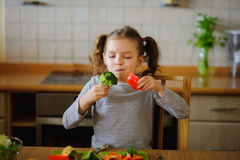 Girl of 8-9 years sits at a kitchen table. Royalty Free Stock Images