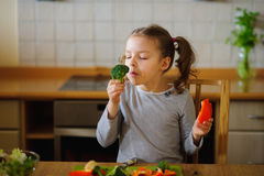 Girl of 8-9 years sits at a kitchen table. Stock Image