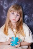 Girl 5 years sits near a window covered with frost. With a cup in his hand Royalty Free Stock Images