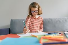 Girl of 8 years sitting on sofa at home drawing writing with pencil in notebook. Child blonde with glasses studying at home.  royalty free stock images