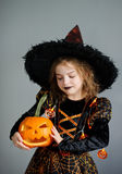 Girl of 8-9 years in a suit for Halloween. Portrait of the girl of 8-9 years in a suit for Halloween. She represents the evel sorcerer. The girl is dressed in a Royalty Free Stock Photography