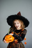 Girl of 8-9 years in a suit for Halloween. Portrait of the girl of 8-9 years in a suit for Halloween. She represents the evel sorcerer. The girl is dressed in a royalty free stock images