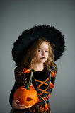 Girl of 8-9 years in a suit for Halloween. Portrait of the girl of 8-9 years in a suit for Halloween. She represents the evel sorcerer. The girl is dressed in a Royalty Free Stock Image