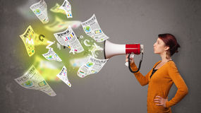 Girl yelling into loudspeaker and newspapers fly out Royalty Free Stock Images