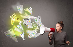 Girl yelling into loudspeaker and newspapers fly out Royalty Free Stock Photos